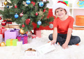 Little boy in Santa hat with milk, cookies and letter for Santa Claus — Stock Photo