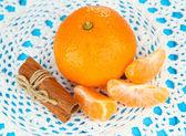 Tasty mandarine on color plate on blue background — Stock Photo