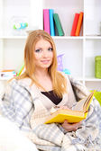 Attractive young woman sitting on sofa and reading book, on home interior background — Stock Photo