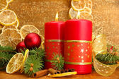 Two candles and christmas decorations, on golden background — Stockfoto