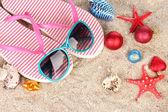 Christmas balls,seashells andh beach accessories on sand, close-up — Zdjęcie stockowe