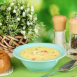 Fragrant soup in blue plate on table on natural background close-up - Stock Photo