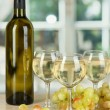 White wine in glass with bottle on window background - Photo