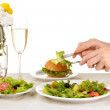 Stock Photo: Female hand with dinner isolated on white