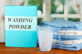 Box of washing powder with blue measuring cup and towels, on wooden table close-up — Stock Photo