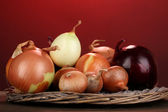 Ripe onions on wicker cradle on wooden table on red background — Stock Photo