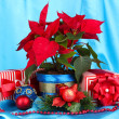 Beautiful poinsettia with christmas balls and presents on blue fabric background — Stock Photo #18320033