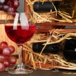 Wooden case with wine bottles, barrel, wineglass and grape on wooden table on grey background — Stock Photo