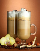 Fragrant coffee latte in glasses cups with spices, on brown background — Stock Photo