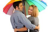 Loving couple with umbrella isolated on white — Stock Photo