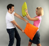 Young couple with pillows on grey background — Stock Photo