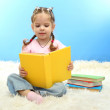 Cute little girl with colorful books, on blue background — Foto de Stock