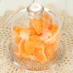 Tangerine on saucer under glass cover on light background — Stock Photo