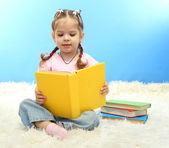 Niña linda con coloridos libros, sobre fondo azul — Foto de Stock