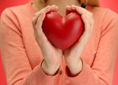 Red heart in woman hands, on red background — Stock Photo