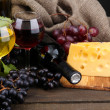 Bottles and glasses of wine, cheese and grapes on grey background — Stock Photo #18354409