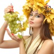 Beautiful young woman with yellow autumn wreath and grapes, isolated on white — Stock Photo #18356867