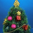 Decorated artificial Christmas Tree on blue background — Stock Photo