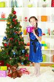 Little girl holding gift box near christmas tree — Stock Photo