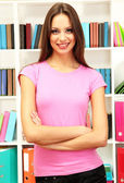 Young attractive female student in library — Stockfoto