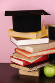 Books and magister cap against school board on wooden table on pink background — Stock Photo