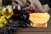 Bottles and glasses of wine, cheese and grapes on grey background — Stock Photo