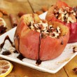 Baked apples on plate on wooden table - Stock Photo