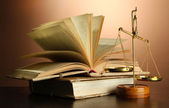 Gold scales of justice and books on brown background — Foto Stock