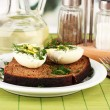 Boiled eggs  on dark bread on green background — Stock Photo
