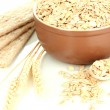 Brown bowl full of oat flakes with spikelets, oat biscuits and wooden spoon isolated on white — Stock Photo