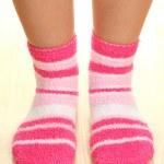 Legs female in striped socks on laminate floor — Stock Photo #18402545