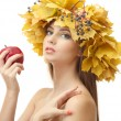 Beautiful young woman with yellow autumn wreath and apple, isolated on white - Stock Photo