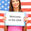 Young woman young woman holding tablet on background of American flag - Stock Photo