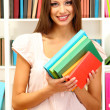 Young attractive female student holding her school books in library — Stock Photo #18402789