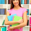 Young attractive female student holding her school books in library — Stock Photo