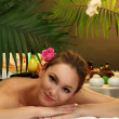 Beautiful young woman in spa salon with spa stones, on green background - Stock Photo