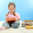 Stock Photo: Cute little girl with colorful books, on blue background