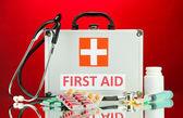 Boîte de premiers soins, sur fond rouge — Photo