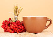 Tea with red viburnum on table on beige background — Stock Photo