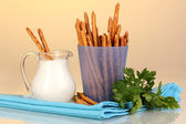 Tasty crispy sticks in purple plastic cup on yellow background — Stock Photo