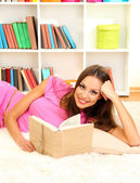 Young female relaxing on floor at home reading book — ストック写真