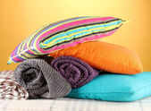 格子布和颜色枕头在黄色背景上 — 图库照片