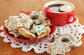 Christmas treats on plate and cup of coffe on wooden table close-up — Stock Photo