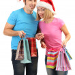 Young couple in Santa hats shopping and holding many shopping bags isolated on white — Stock Photo #18427687