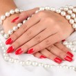 Female hands holding beads on color background — Stock fotografie