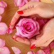 Woman hands with wooden bowl of water with petals - Stockfoto