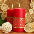 Two candles and christmas decorations, on golden background — Stock Photo #18427109