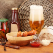 Beer and grilled sausages on wooden table on  sackcloth background — Stock Photo