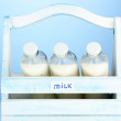 Milk in bottles in wooden box on blue background — Stock Photo