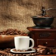 Coffee grinder and cup of coffee on burlap background - Stock Photo